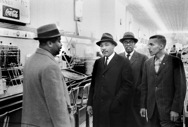 Garson McLeod Sr. ( a Durham County Sheriff Deputy), Dr. Martin Luther King, Jr., Rev. Douglas Moore, pastor of the Asbury Temple Methodist Church (Durham) and NCCU student, Lacy Streeter visits Woolworths in downtown Durham February 16 1960.