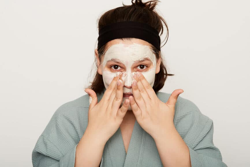 woman washing face with mask practicing self care during Capricorn season wellness routine