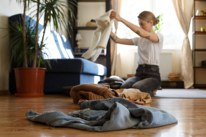 woman sorting through her clothing to give to others for her Leo full moon ritual article by the astrotwins