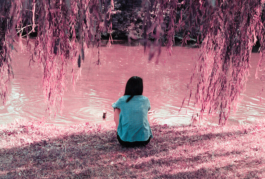 woman sitting on river bank reflecting at the 2020 pisces new moon