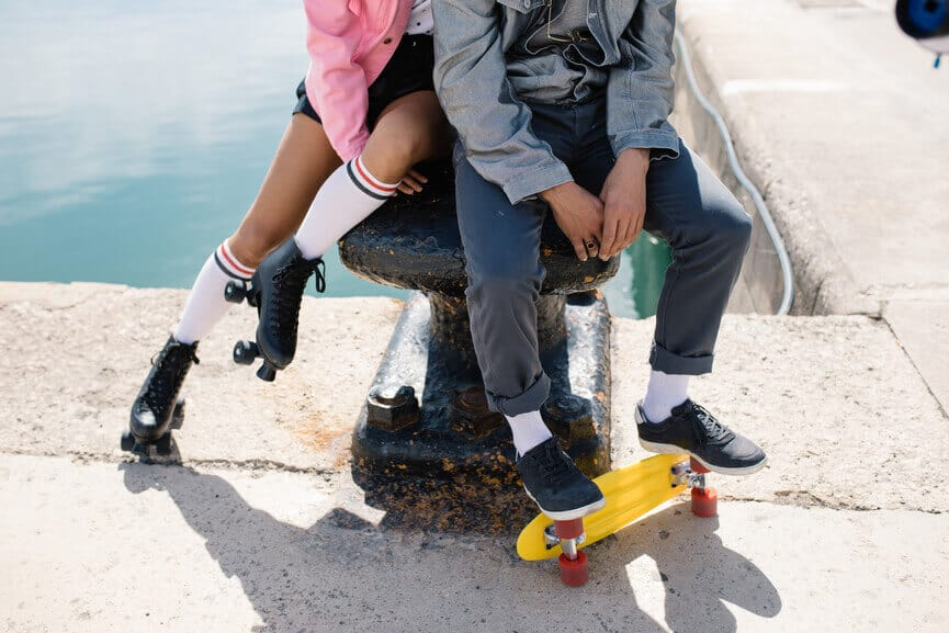 man and woman sitting cozy with skateboard for valentine's day and 2020 astrology love forecast by the astrotwins on astrostyle