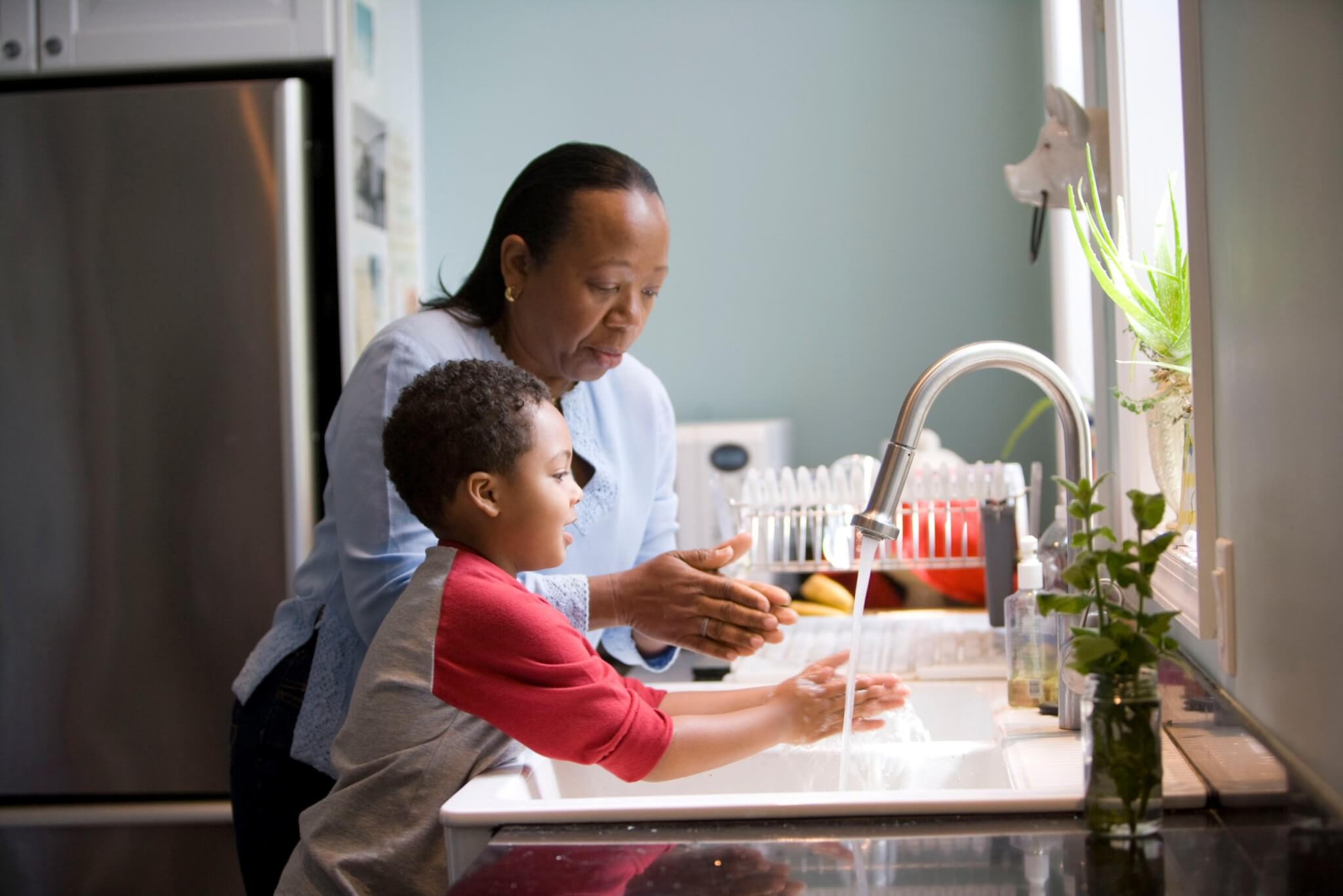 woman washing hands with her son during the coronavirus outbreak showing the balance of life and work and family dynamics by zodiac sign during coronavirus article by the astrotwins for astrostyle.com
